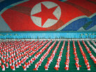 The Arirang mass festival re-enacts the history of North Korea. The flag depicted in the background was created by audience members holding up cards.