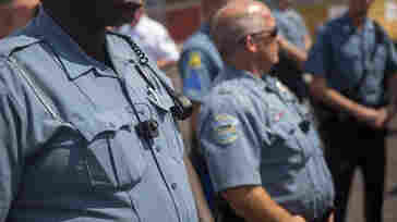 Members of the Ferguson Police Department wear their new body cameras during a rally Aug. 30, in Ferguson, Mo.