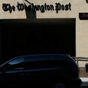 A man walks past the Washington Post building on Tuesday in Washington, D.C.