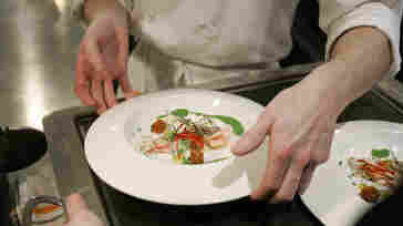 Chef Grant Achatz places one of many courses on a server's tray in the Alinea restaurant kitchen in Chicago in 2008. In 2012, the restaurant got rid of reservations and started selling tickets. Earlier this summer, the company announced how effective it's been.