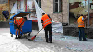 Street sweepers clean up broken glass and debris after a Ukrainian army artillery attack in late August on Russian-backed separatist fighters in Donetsk. One street sweeper was killed in late July by shelling — but the need for a paycheck and the pride they take in their city is what keeps city government workers like these returning to work each day.