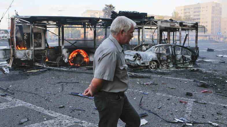 A man walks past burnt vehicles near a railway station after recent shelling in Donetsk, eastern Ukraine, Aug. 29.