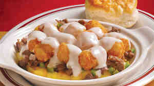 One of Huddle House's signature dishes is the Philly Cheese Steak Tots: steak covered with cheddar cheese sauce and shredded cheese, on an open-faced omelet with Tater Tots.