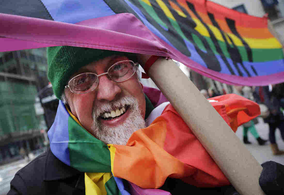 """Artist Gilbert Baker, designer of the Rainbow Flag, is draped with the flag while holding a banner that reads """"Boycott Homophobia"""" before the start of the St. Patrick's Day parade in March in New York."""