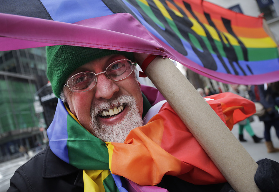 """Artist Gilbert Baker, designer of the Rainbow Flag, is draped with the flag while holding a banner that reads """"Boycott Homophobia"""" before the start of the St. Patrick's Day parade in March in New York. (Mark Lennihan/AP)"""