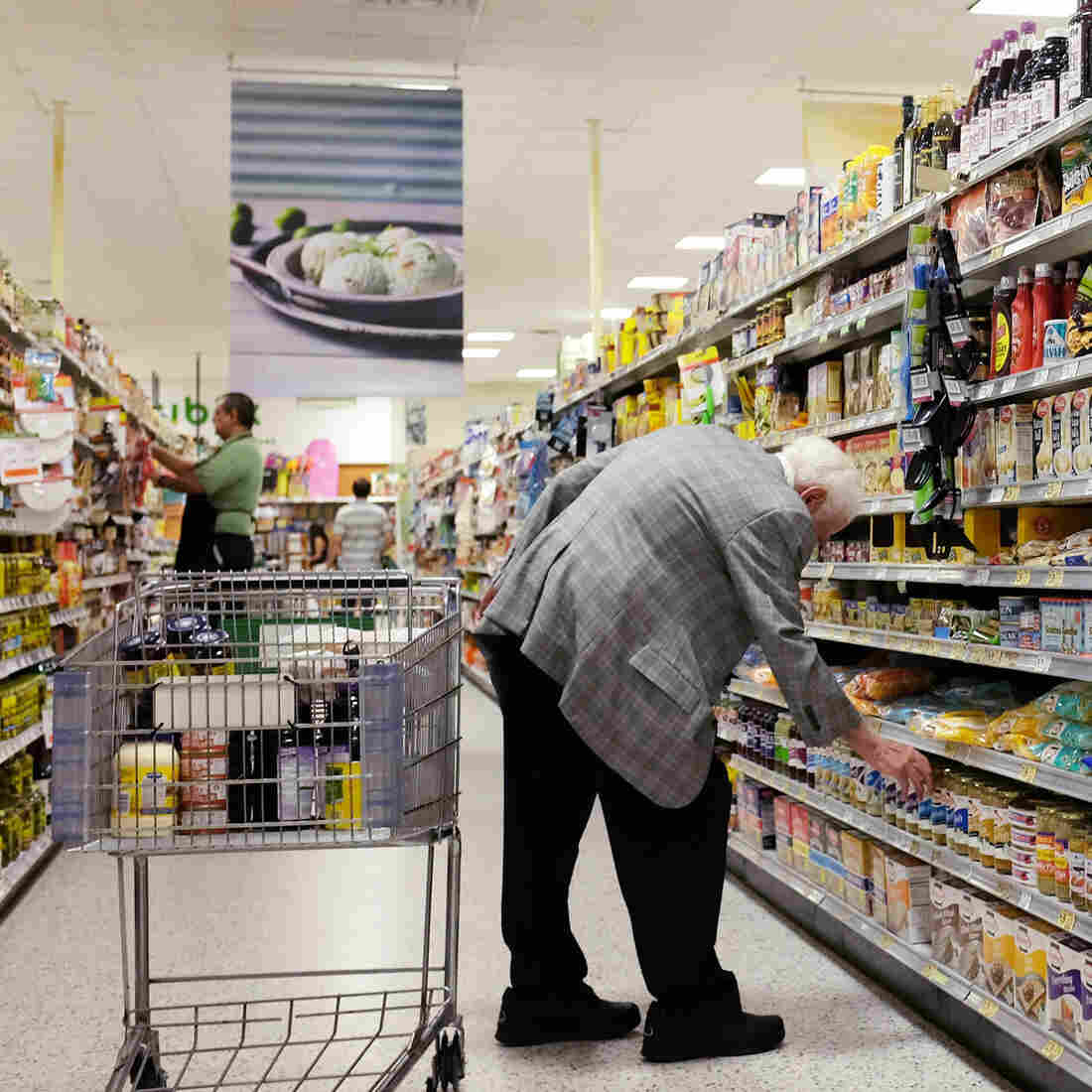 People shop in a Miami grocery store on July 8. USDA says that despite the drop in unemployment, the number of food insecure Americans has not declined because higher food prices and inflation last year offset the benefits of a brighter job market.