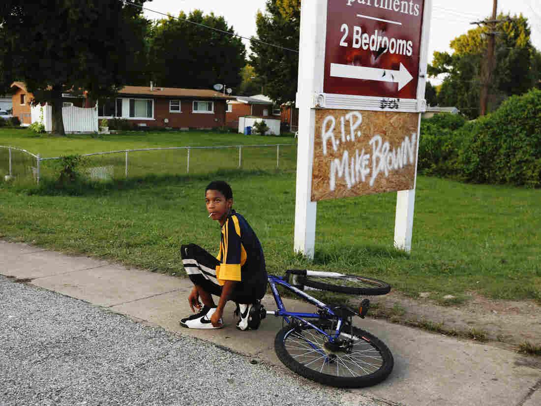 A kid stops to tie his shoe along West Florissant Avenue.