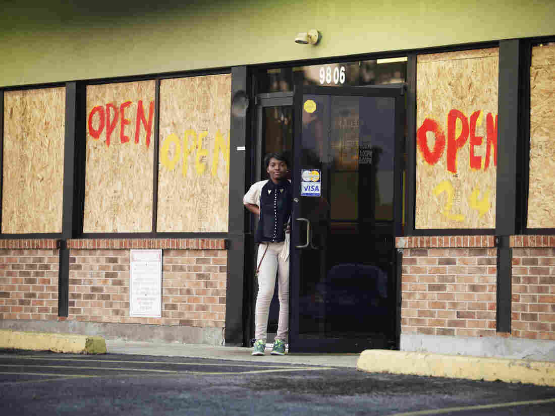 A woman stands in front of a restaurant on West Florissant Avenue where rioting took place last month. Most of the stores on this stretch are boarded up — some after they were damaged by looters, and some as a precaution.