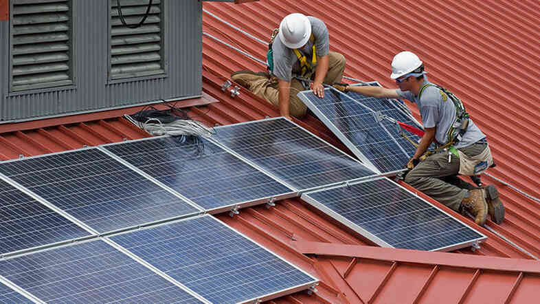 Construction workers installing a solar panel.