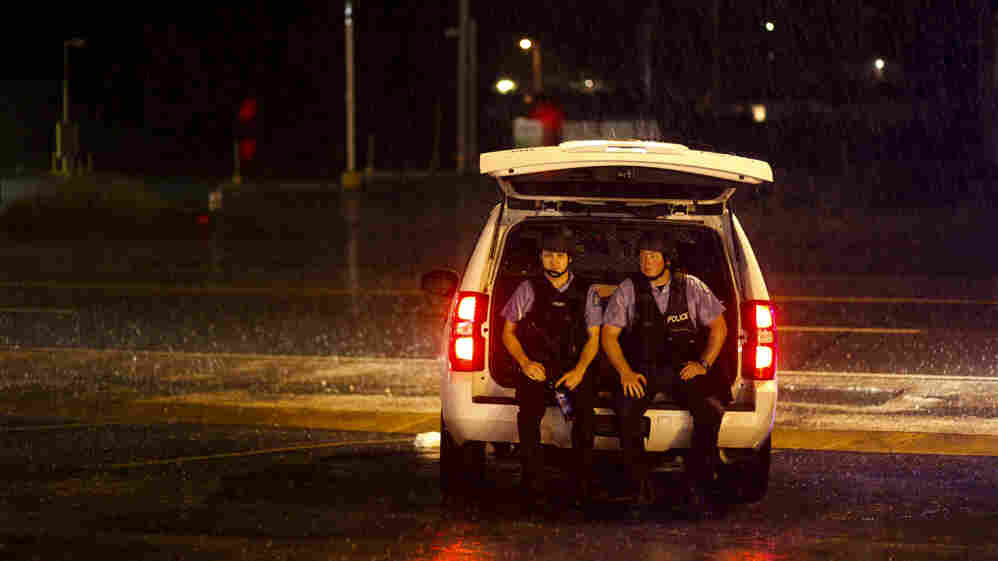 Two police officers waited out a passing thunderstorm along the protest route.