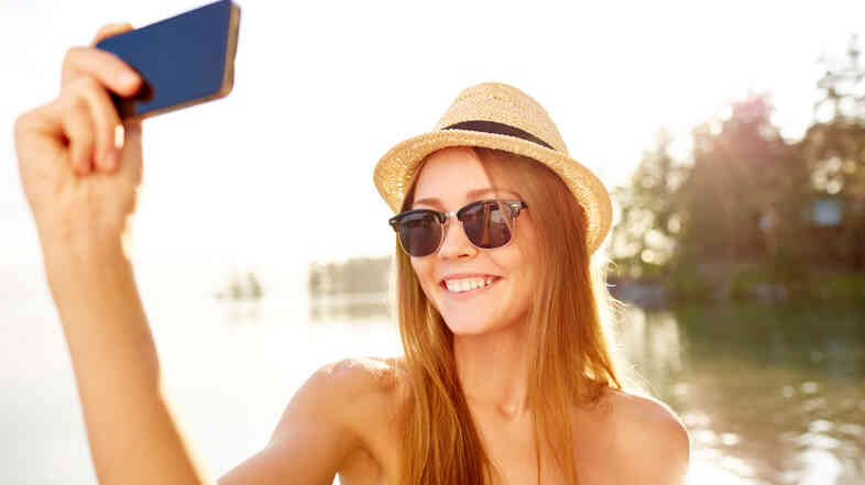 Cheerful girl taking a selfie on the beach.