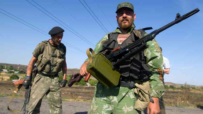 Pro-Russian separatists stand on a road in the village of Novokaterinovka, eastern Ukraine, on Thursday.