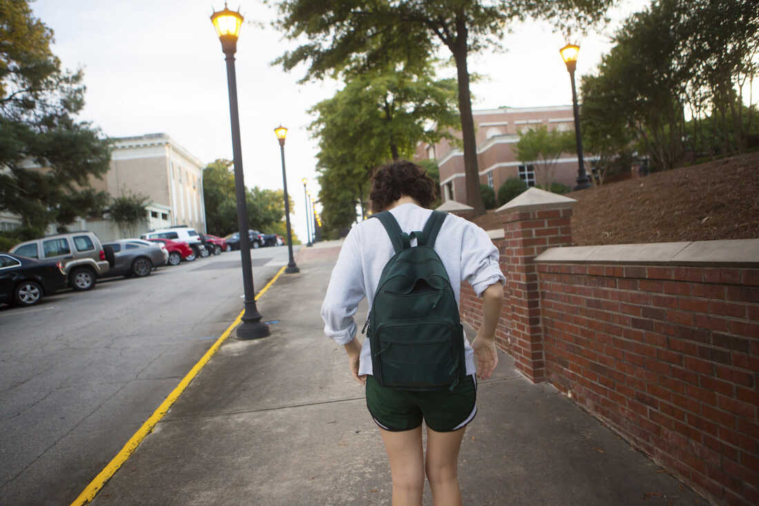 Student walking on campus with a bookbag.