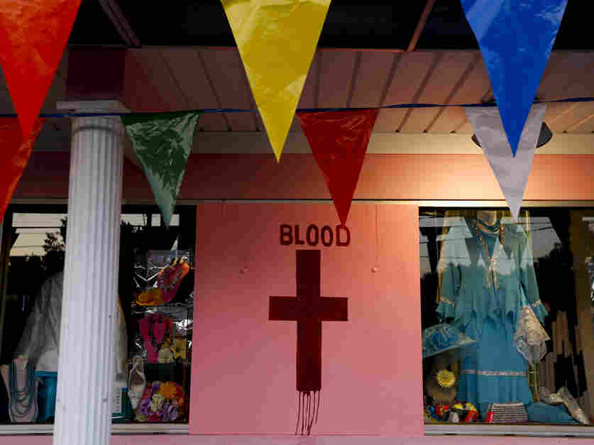 """Many of the shops on the protest route were temporarily closed. This cross is the third in a series of pictures on this store's wall. Together, they read: """"Oh The Blood."""""""
