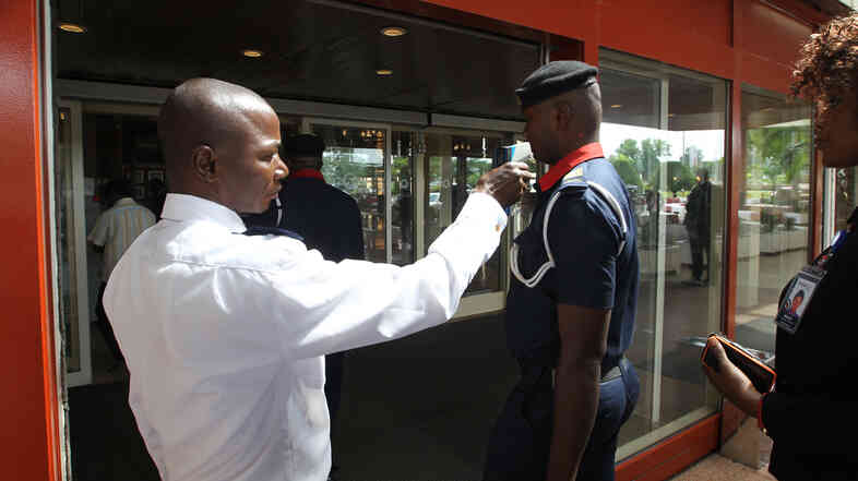 A security man takes visitors' temperatures Wednesday at the Transcorp Hilton hotel in Abuja, Nigeria, about 400 miles north of Port Harcourt.