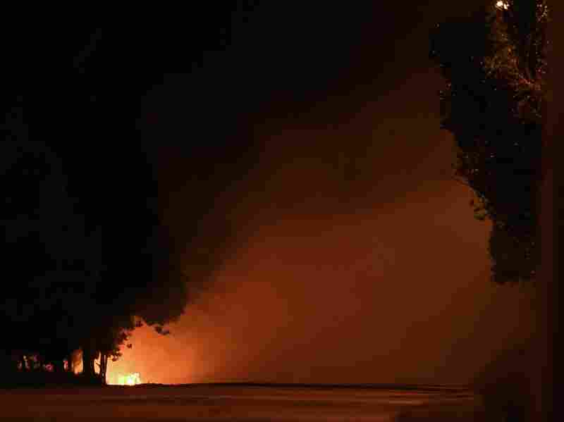 A Ukrainian army checkpoint burns on the road to Russia after loud explosions were heard on the outskirts of Mariupol late Saturday.