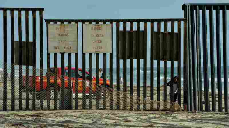 A man looks out towards the US from the Mexican side of the border fence that divides the two countries in San Diego. The U.S. Border Patrol says it has seen about a 60 percent drop in the number of Central Americans apprehended at the border.
