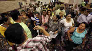 People wait to sign up for unemployment Sept. 3 at the Atlantic City Convention Center in Atlantic City, N.J., where thousands of workers at the closing Revel and Showboat casinos recently were laid off.