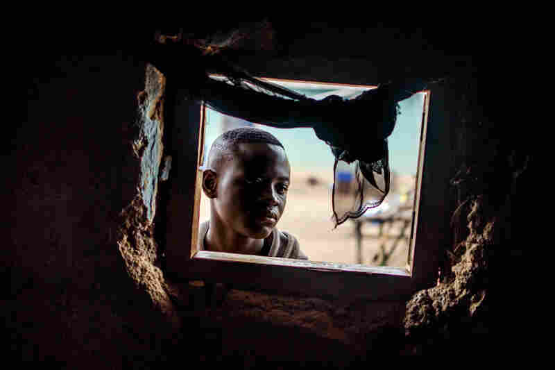 Alieu P. Manor, 18, survived Ebola. He gazes into the room of his cousin, Varlee Kanneh, who was not so lucky.