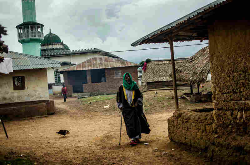 The chief imam of Barkedu, a predominantly Muslim town, walks down an empty street.