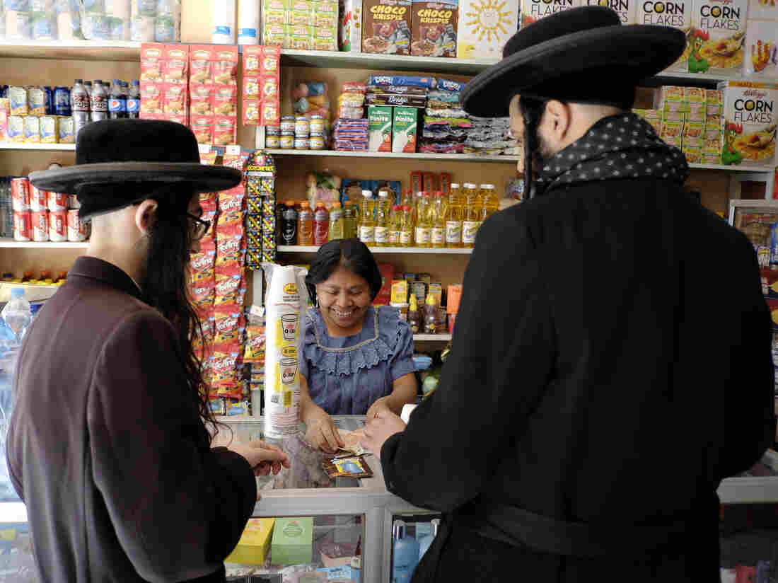 Men from Lev Tahor shop in San Juan, Guatemala. In a culture of brightly colored clothing and clean-shaven men, the black suits and long beards stood out.