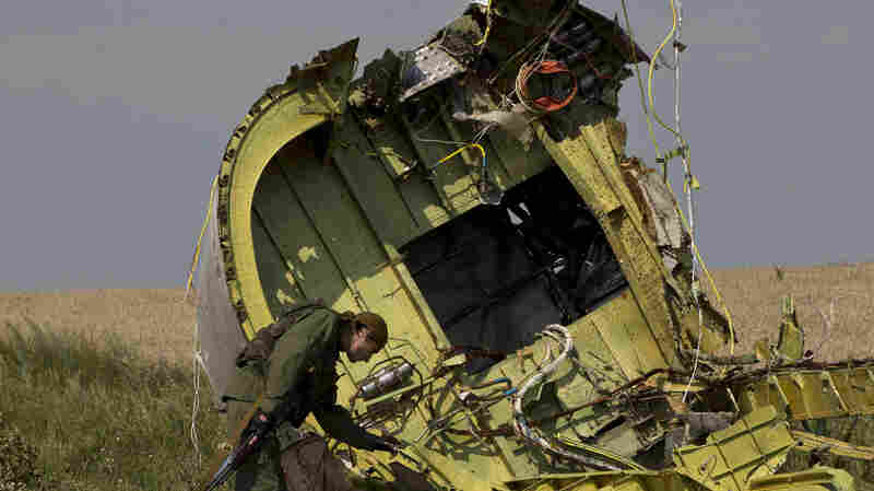 A pro-Russian rebel touches MH17 wreckage at the crash site of the Malaysian airliner near the village of Hrabove, eastern Ukraine, in July.