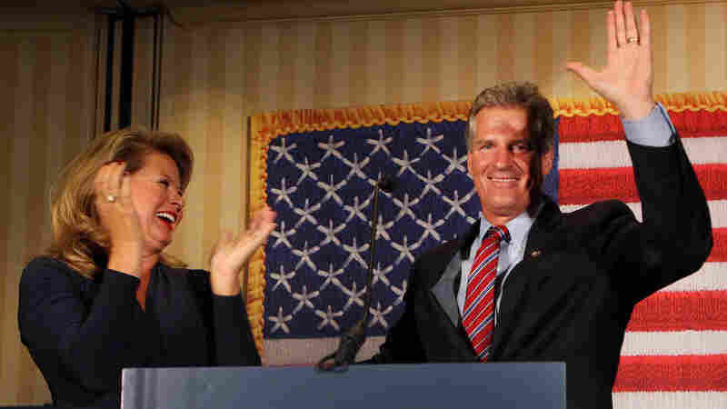 Scott Brown, right, a former U.S. Senator from Massachusetts, waves to supporters as his wife Gail, left, claps after he won New Hampshire's Republican U.S. Senate primary on Tuesday in Concord, N.H.