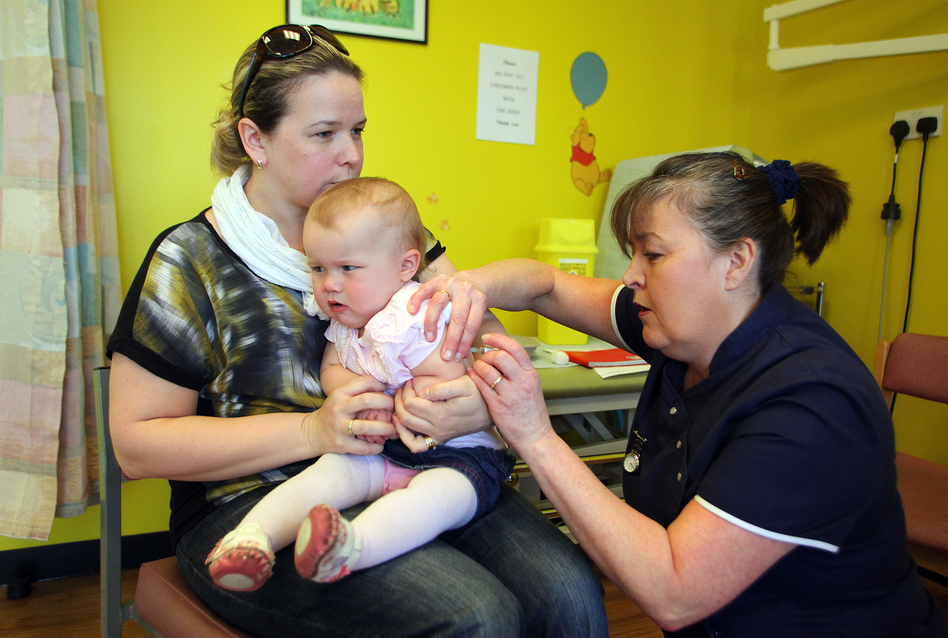 Helen Down holds her 14-month-old daughter, Amelia, for an MMR shot in Swansea, Wales, April 2013. The vaccination was in response to a measles outbreak. (Geoff Caddick/AFP/Getty Images)