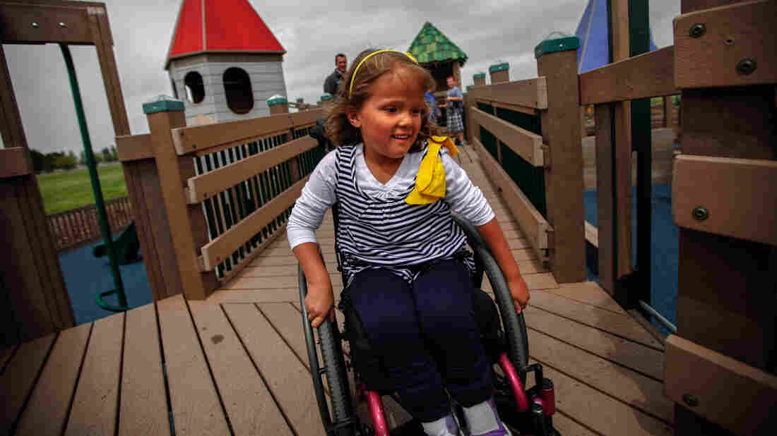 Brooklyn Fisher rolls down the ramp on the playground named for her in Pocatello, Idaho. The playground was built using accessible features so children of all abilities could play alongside each other.