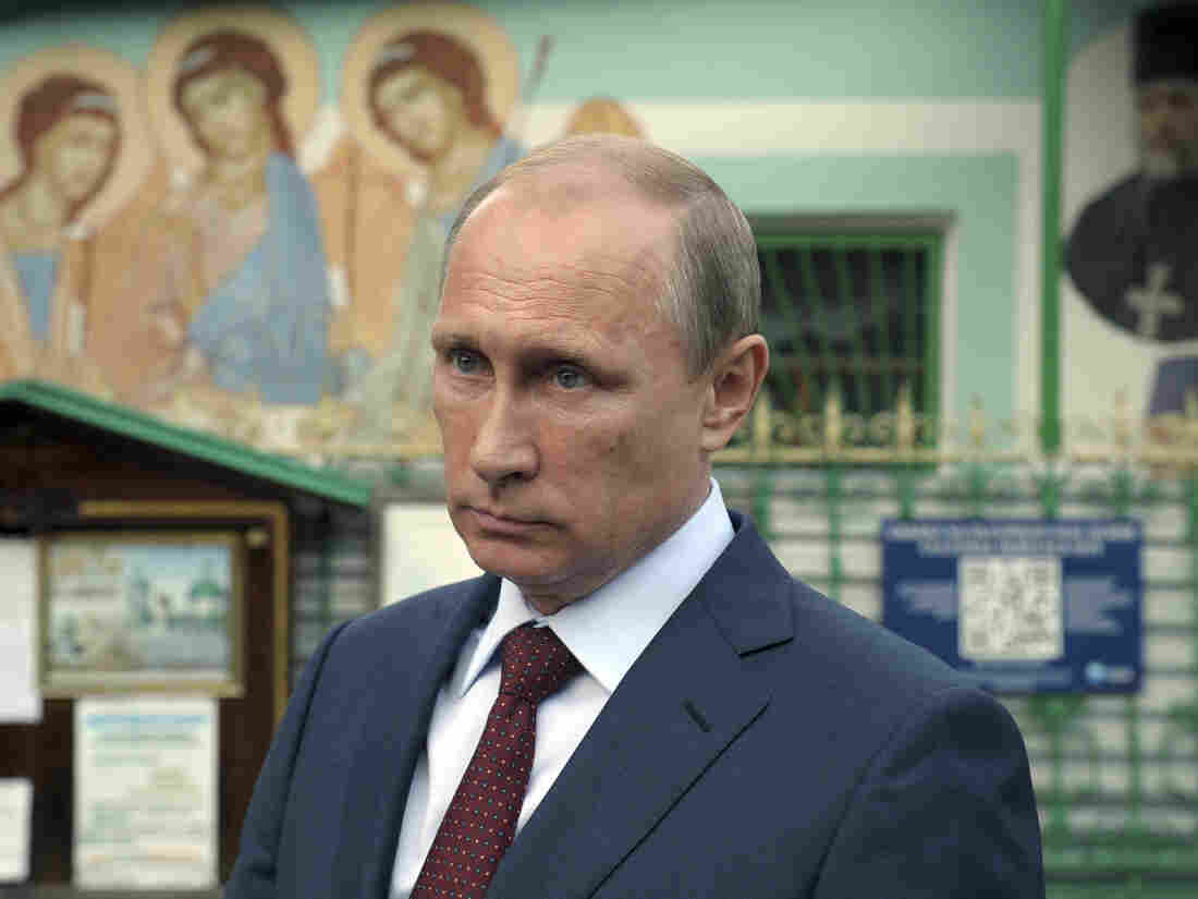 """Russian President Vladimir Putin leaves the Life-giving Trinity church in Moscow, on Wednesday. Putin accused NATO of using the Ukraine crisis to """"resuscitate itself."""""""