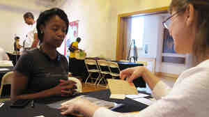 Neonta Williams (left) shares family letters dating back to 1901 with preservationist Kimberly Peach during the Smithsonian's Save our African American Treasures program at the Birmingham Civil Rights Institute. Peach advises her to use archive-quality polyester sleeves to protect the fragile papers, rather than store them in a zip-lock bag.