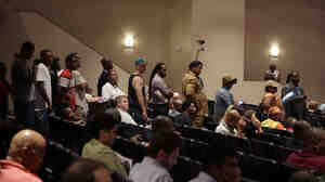 A line of people wait to speak during a meeting of the Ferguson City Council on Tuesday. The meeting was the first for the council since t