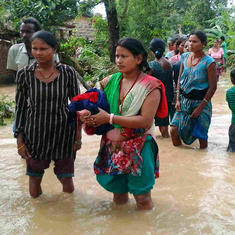 Families carry their belongings while moving to higher ground in the Bardia region of Nepal during the flooding on Aug. 15.