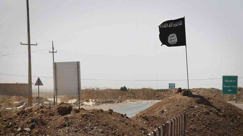 A flag of the Islamic State — aka ISIS, aka ISIL — is seen on the other side of a bridge at the front line of fighting between Kurdish Pesh Merga fighters and Islamist militants in Rashad, Iraq, on Thursday. The group is referred to differently depending on who's talking about it.