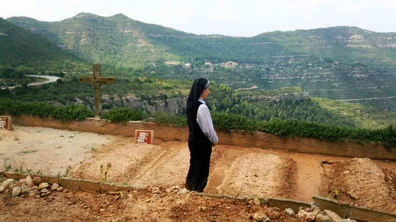 Sister Teresa Forcades prays over the graves of fellow nuns in a cemetery at her Sant Benet Monastery in Montserrat, Spain.
