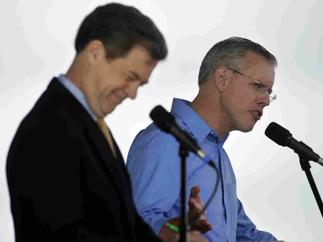 Republican Gov. Sam Brownback (left) listens while his Democratic challenger Paul Davis answers a question during their first debate at the Kansas State Fair.