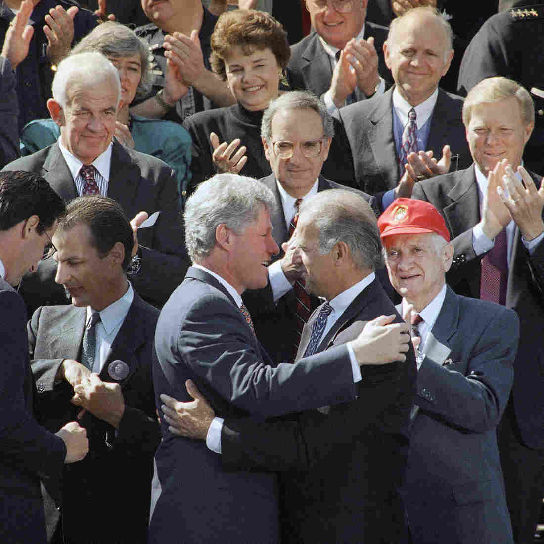 Surrounded by lawmakers, President Bill Clinton hugs then-Sen. Joseph Biden after signing the $30 billion crime bill at the White House on Sept. 13, 1994.