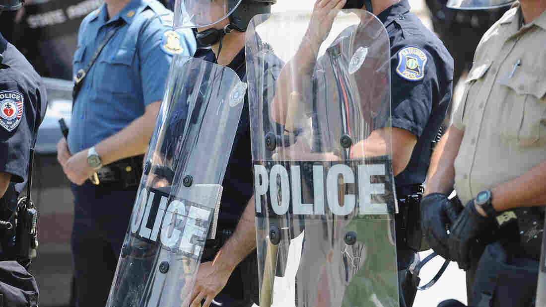 Police officers equipped in riot gear line up during a protest of the shooting death of 18-year-old Michael Brown outside Ferguson Police Department Headquarters on Aug. 11, 2014, in Ferguson, Mo.