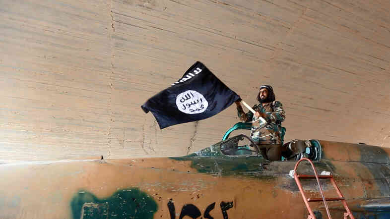 This image, posted on a militant website, shows an Islamic State fighter waving a flag from a captured government fighter jet in Raqqa, Syria. The Islamic State captured the city in northeastern Syria last year and it has effectively served as its capital.