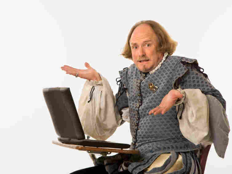 William Shakespeare in period clothing sitting in school desk with laptop computer shrugging at viewer.