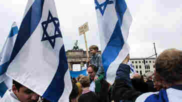 People with Israeli flags and banners attend a rally against anti-Semitism near the Brandenburg Gate in Berlin on Sunday.