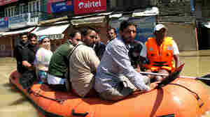 Small boats operated by the National Disaster Response Force ferry flood victims in Kashmir on Saturday.