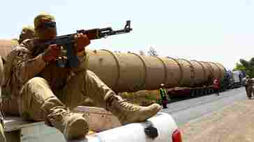 A soldier guards a pipe en route to an the Kawergosk Refinery near Erbil, the capital of the autonomous Kurdish region of northern Iraq, in July. Fighting in northern Iraq forced the closure of the country's largest oil refinery, Baiji, and cut production from the Kirkuk oil field this summer.