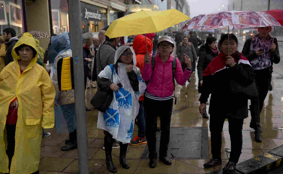 A tourist wears a poncho decorated with the national flag of Scotland to shelter from the weather in Scotland's capital, Edinburgh, on Monday.