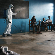 A health worker speaks with families in a classroom now used as Ebola isolation ward in Monrovia, Liberia. Ebola-stricken West Africa needs more health staff and more medical facilities.