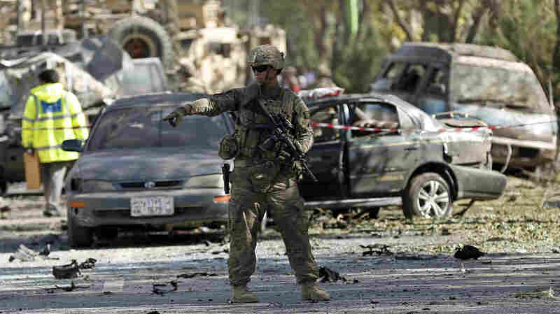 A U.S. soldier stands guard near a damaged vehicle at the site of a suicide attack in Kabul on Tuesday.