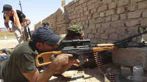 Members of Iraqi security forces are seen during a fight with Islamic State militants Sunday on the outskirts of the city of Ramadi.