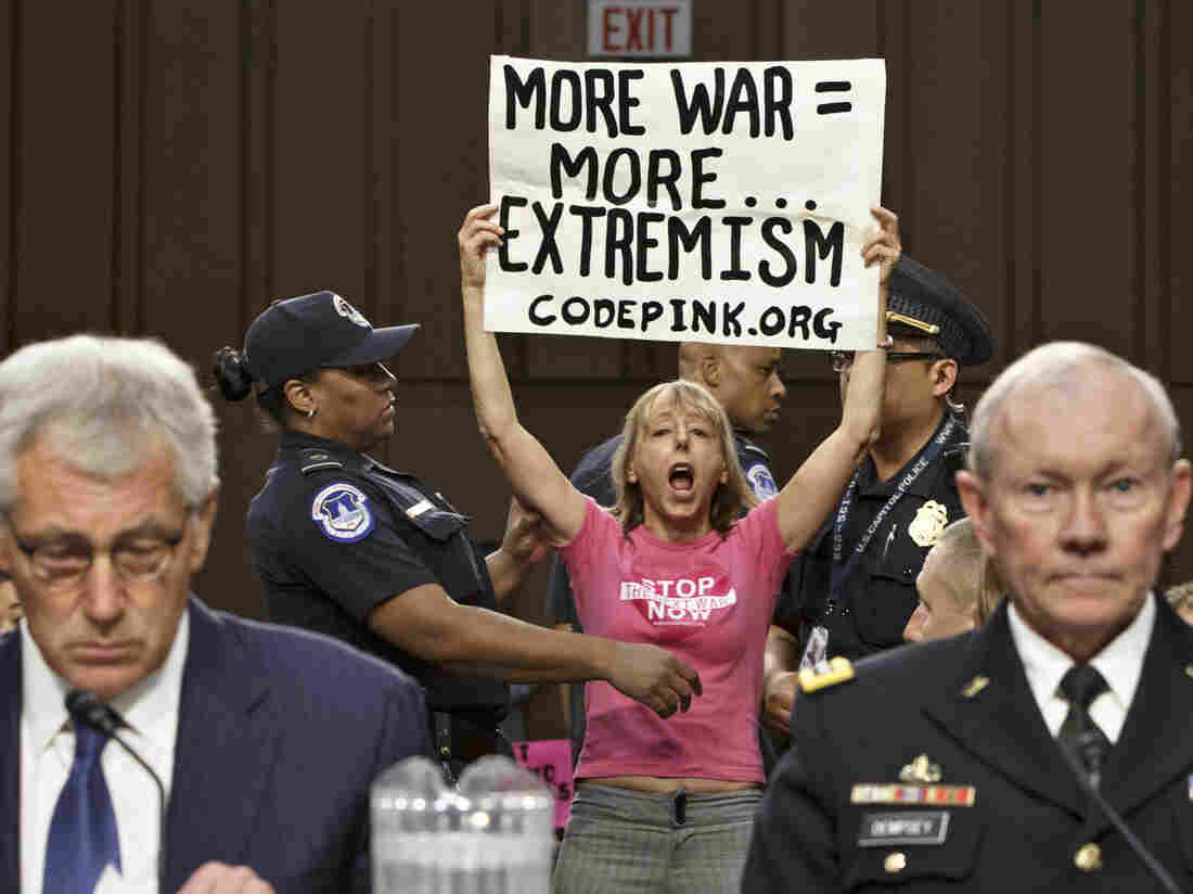 Members of the anti-war activist group CodePink interrupt a Senate Armed Services Committee hearing with Defense Secretary Chuck Hagel (left) and Gen. Martin Dempsey, chairman of the Joint Chiefs of Staff.