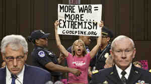 Members of the anti-war activist group CodePink interrupt a Senate Armed Services Committee hearing with Defense Secretary Chuck Hagel, left, and Army Gen. Martin Dempsey, chairman of the Joint Chiefs of Staff.