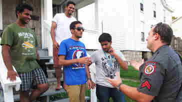 """Frostburg State University police officer Derrick Pirolozzi, right, conducts a """"knock and talk"""" at a house near campus, reminding students of laws on underage drinking and open containers."""